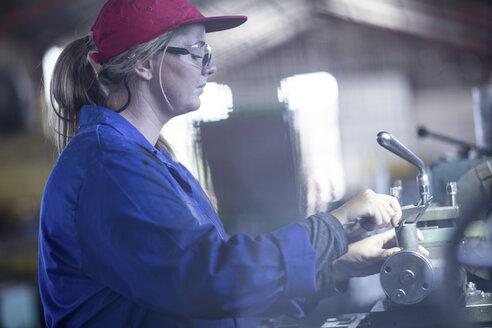 Woman using Vernier caliper in workshop - ZEF12117