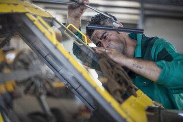 Mechanic in hangar repairing light aircraft - ZEF12150