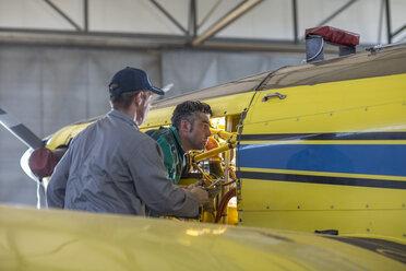 Mechanics in hangar repairing light aircraft - ZEF12153