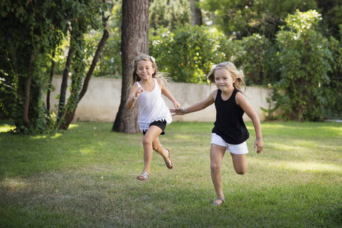 Two little sisters running and racing in the garden - LITF00465