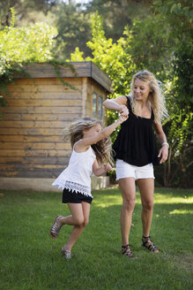 Mother and her little daughter dancing together in the garden - LITF00471