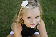 Portrait of blond little girl on a meadow wearing flowers - LITF00477