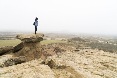 Spain, Navarra, Bardenas Reales, young woman standing on rock in nature park looking at view - KKAF00251