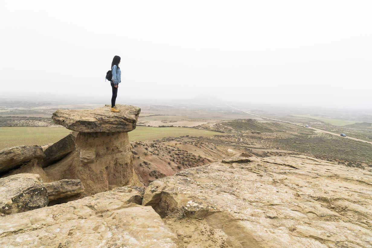 Spain, Navarra, Bardenas Reales, young woman standing on rock in nature park looking at view - KKAF00251 - Kike Arnaiz/Westend61