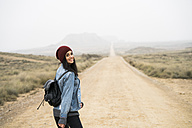 Spain, Navarra, Bardenas Reales, smiling young woman walking in nature park - KKAF00257