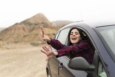 Spain, Navarra, Bardenas Reales, screaming and waving young woman leaning out of car window - KKAF00263
