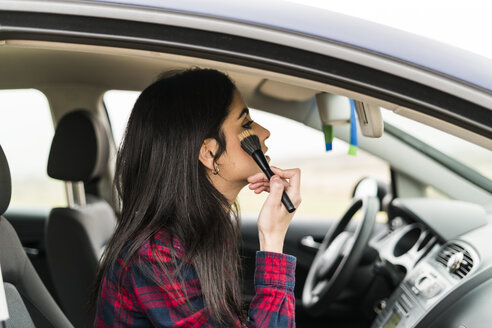 Young woman applying make up on passenger seat of a car - KKAF00269