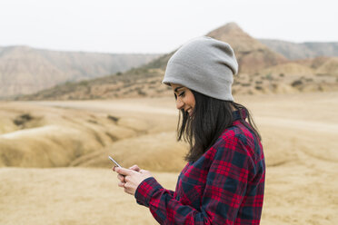 Spain, Navarra, Bardenas Reales, smiling young woman looking at cell phone in nature park - KKAF00272