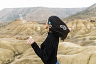Spain, Navarra, Bardenas Reales, young woman blowing soap bubbles - KKAF00281