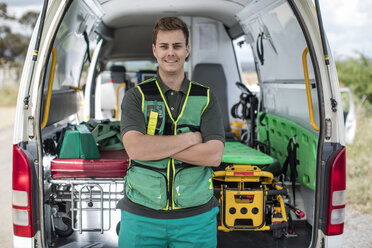 Paramedic standing with arms crossed in front of ambulance - ZEF12173
