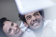Smiling young couple together in bed with a tablet - ZEF12188