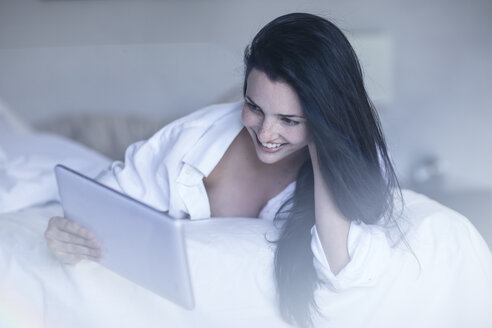 Smiling young woman in bed using tablet - ZEF12194