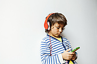 Little boy listening to the music of his smartphone with headphones - VABF00973