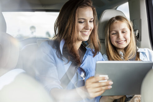 Mother and daughter on road trip sitting in car looking at digital tablet - WESTF22345