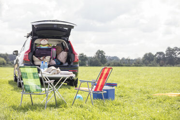 Car on meadow with open boot full of luggage - WESTF22375