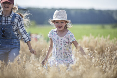 Two laughing girls running in field - WESTF22387