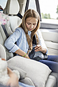 Girl sitting in car, fastening seat belt - WESTF22402