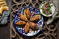 Kibbeh, oriental meat croquettes with yoghurt sauce on plate - SBDF03111