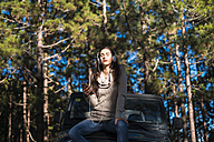 Young woman with eyes closed sitting on car bonnet in the forest listening music with headphones - SIPF01236