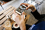 Woman in pavement cafe taking picture of her breakfast with cell phone - VABF00994