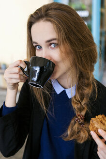 Young woman with muffin drinking cup of coffee - VABF00997