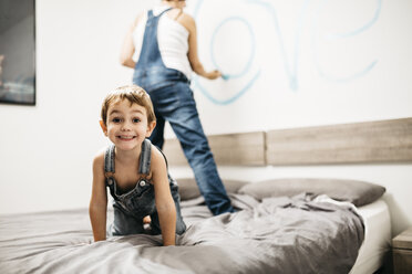 Portrait of little boy playing on bed while his mother painting the wall - JRFF01126