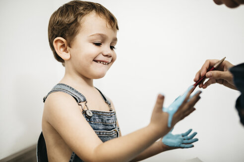 Mother painting little boy's hands blue - JRFF01135