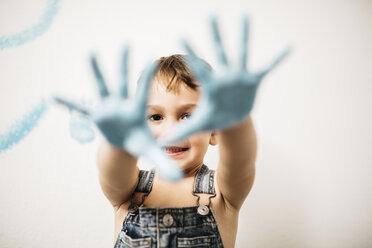 Portrait of smiling little boy showing his palms full of light blue colour - JRFF01138