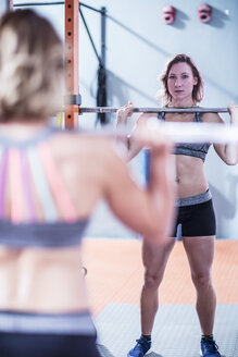 Young woman lifting barbell in gym - ZEF12258