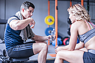 Young man and woman having a refreshment break in gym - ZEF12270
