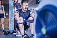 Young man exercising at rowing machine in gym - ZEF12273