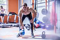 Young man lifting kettlebell in gym - ZEF12279