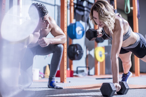 Fitness instructor with woman doing dumbbell press ups in gym - ZEF12282