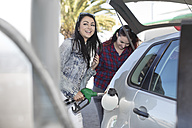 Two women fueling car at gas station - ZEF12294