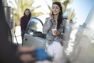 Young woman with takeaway coffee and cell phone at gas station - ZEF12297