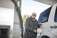 Elderly man fueling car at gas station - ZEF12300