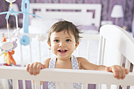 Portrait of happy baby boy in cot - JASF01410