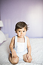 Portrait of baby boy kneeling on bed - JASF01413