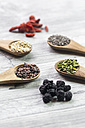 Wooden spoons of chia, cocoa, quinoa and moringa with chokeberries in the foreground - SARF03106