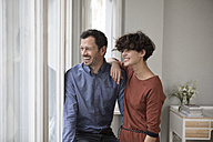 Laughing couple looking through window at home - RBF05422