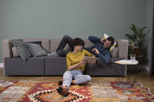 Couple relaxing together in the living room looking at tablet - RBF05449