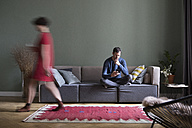Man sitting on the couch in the living room while his girlfriend passing in the foreground - RBF05452