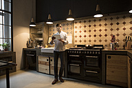 Man standing in the kitchen using tablet - RBF05473