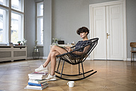 Young woman sitting on rocking chair at home reading a book - RBF05503