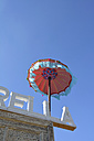 Fringed parasol at roof of a house in front of blue sky - AXF00791