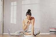Pensive young woman sitting on the floor with laptop making notes - FMKF03392