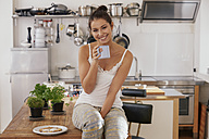 Young woman drinking coffee in kitchen - FMKF03404