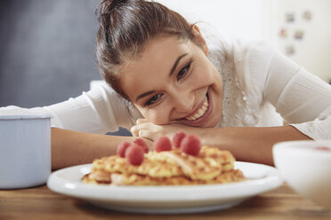 Portrait of happy young woman looking at waffles in the kitchen - FMKF03413