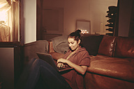 Young woman relaxing with laptop in the lighted living room - FMKF03419