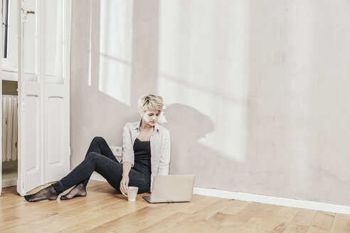 Woman sitting on the floor with coffee cup using laptop - FMKF03443